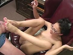 Veronica Jett gives guy a footjob in an office