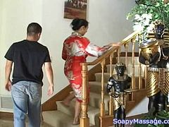 Asian MILF with big tits gives a lucky dude a soapy handjob