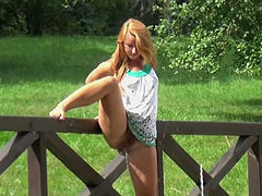 Red haired beautiful chick makes piss on green grass