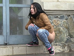Seductive dark haired girl makes piss outdoors during rainy day
