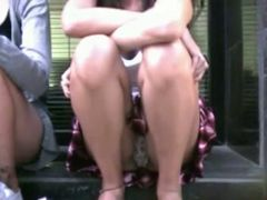 Amazing upskirt sexy girl sitting in the street with her pussy exposed