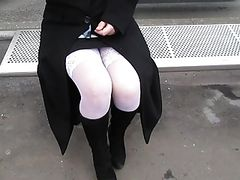 Girl in white stockings on a bus stop