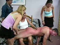 Four sexy chicks spank a guy in a living room