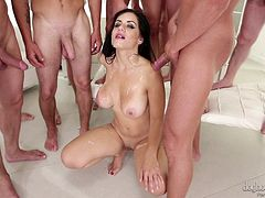 Multiple guys stand around her and shower her face with jizz