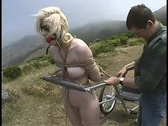 A master makes his female slave pull him in a cart while she is nude